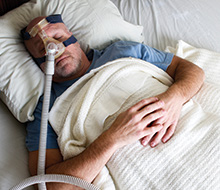 Man with CPAP nasal mask and oral appliance