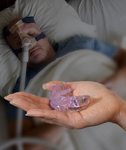 Man with a CPAP mask and hand holding an oral appliance