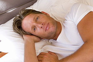 Frustrated man awake in bed
