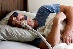 Man with CPAP nose mask sleeping soundly