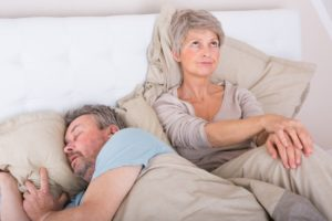 older man sleeping wife upset