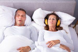 woman wearing headphones husband suffering from sleep apnea in columbus