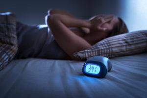 Woman with sleep apnea awake in bed at night
